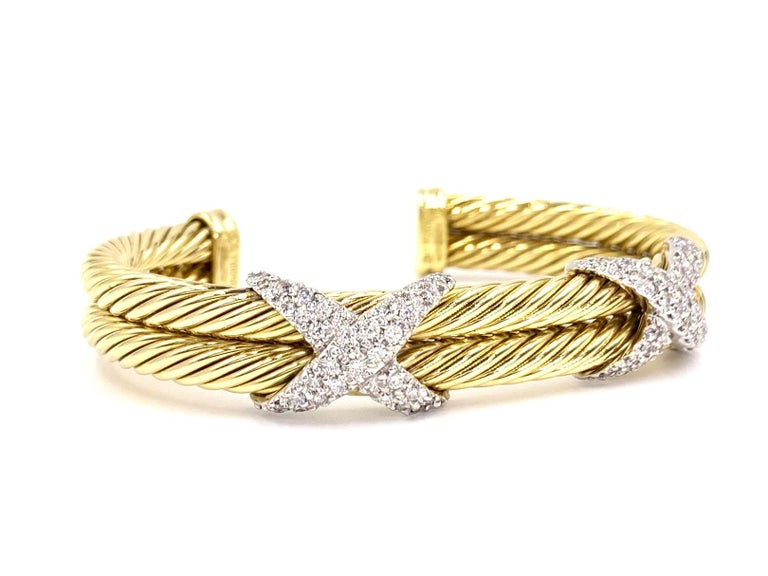 Signed David Yurman 18 karat yellow gold 10mm double cable oval cuff bracelet featuring two pavé diamond X's with approximately 1.50 carats total weight at approximately F-G color, VS2 clarity. Diamonds are set with white gold white gold prongs for