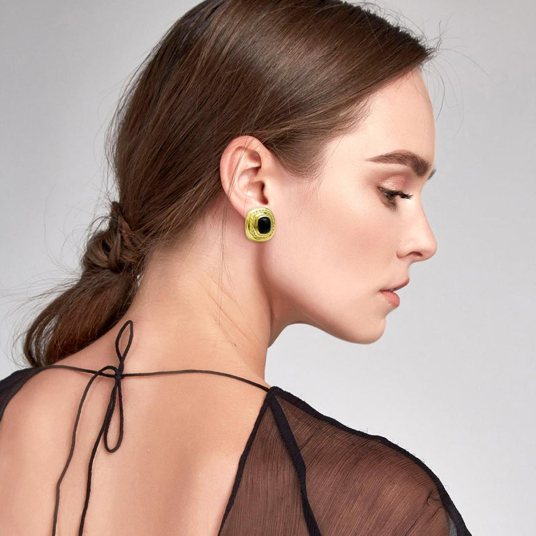Vintage David Yurman stud earrings crafted in 18k yellow gold with a cabochon-cut black onyx center. From the Albion collection. Omega backs.