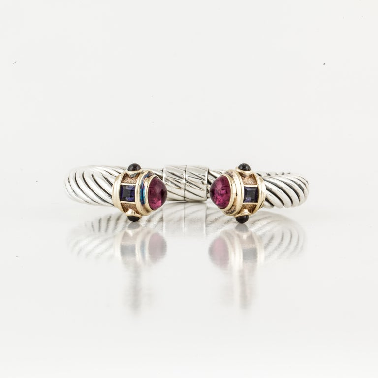 Sterling silver and 14K yellow gold classic cable cuff bracelet by David Yurman.  Features two (2) square faceted iolites, four round cabochon amethysts and two round cabochon pink tourmalines.  Hinged at the bottom.  Measures 2 1/8 inches at the
