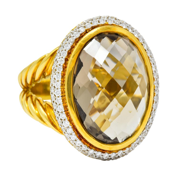 Centering an oval checkerboard cut topaz measuring approximately 18.0 x 13.0 mm, transparent and very light golden color  Bezel set in a polished gold surround with halo of pavé set round brilliant cut diamonds weighing approximately 1.00 carat