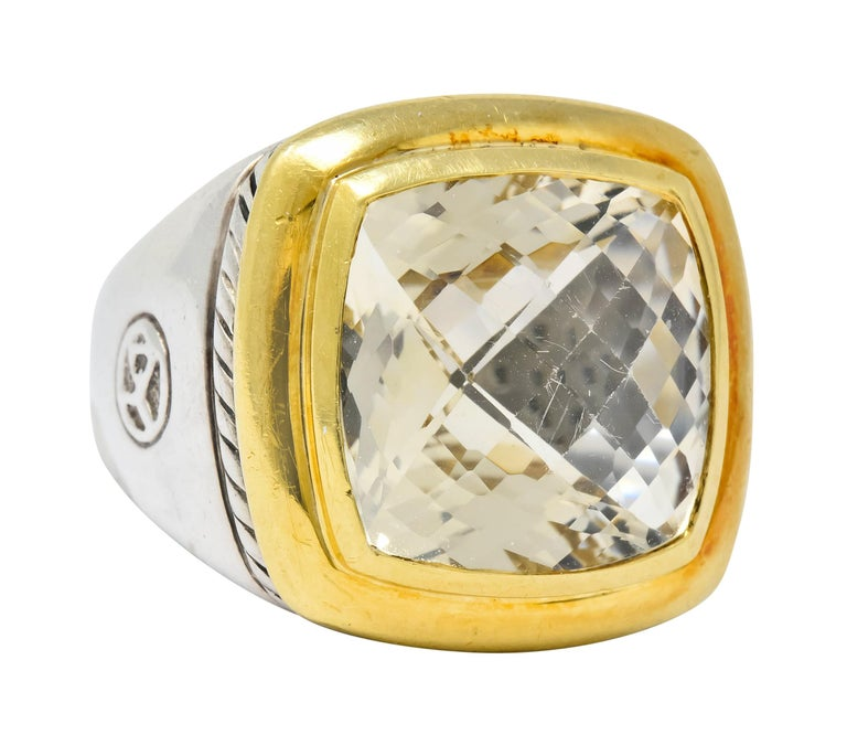 Centering a cushion cut checkerboard colorless quartz measuring approximately 14.0 x 14.0 mm  Bezel set in a polished gold surround offset by twisted cable motif deeply engraved into silver mounting  One shoulder features a highly rendered maker's