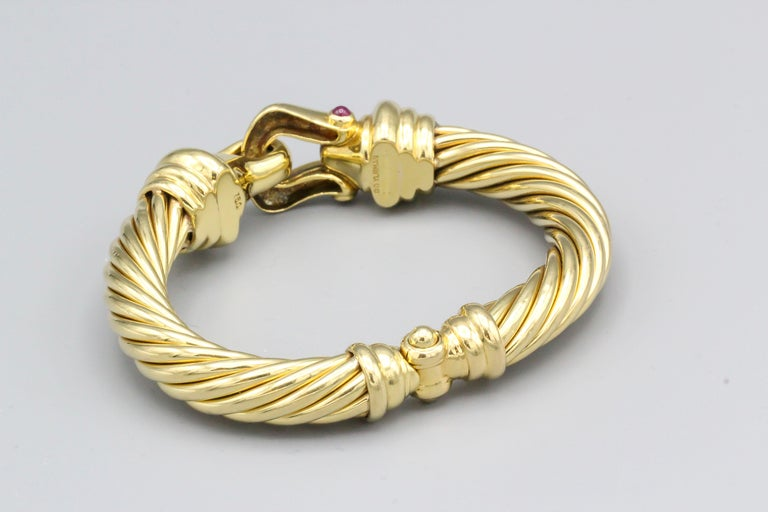 Elegant ruby and 18K yellow gold cuff bracelet by David Yurman. It features a twisted cable design, with two cabochon rubies set on the front buckle.  Cable link approx. 9 mm wide. Similar example with diamonds currently retails for $10500. It is a