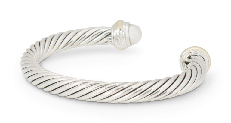 Authentic David Yurman Cable bracelet created in sterling silver with 14 karat gold accents and featuring 2 pearls measuring approximately 7mm each.  Bracelet measures 2 1/4 inches in diameter and can fit up to a size 6 1/2 wrist.  Signed 14K,
