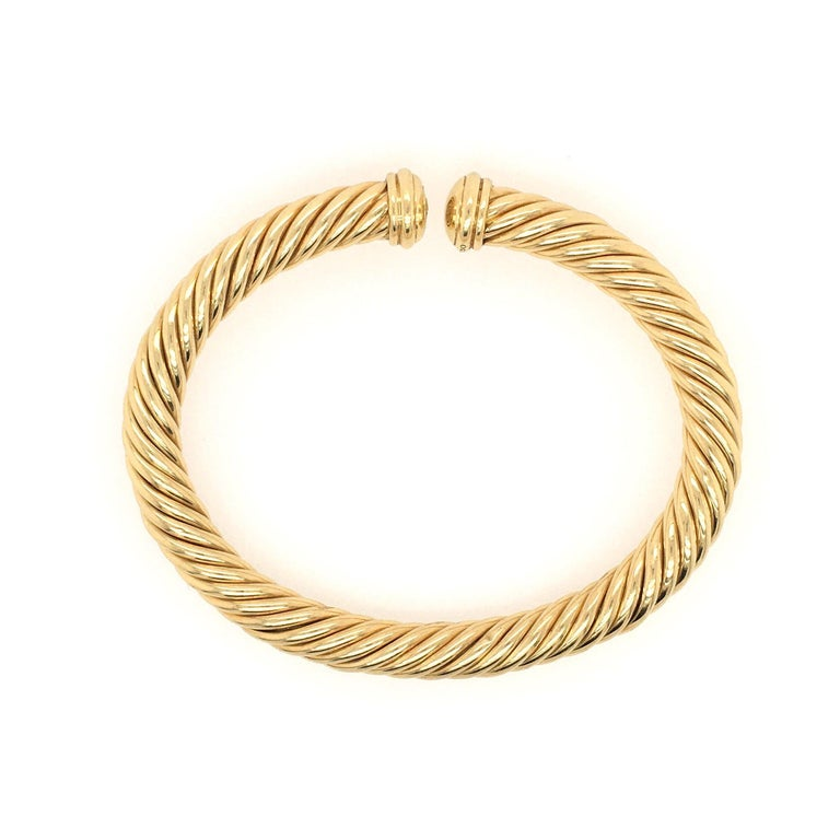 An 18 karat yellow gold Cable Spira Bracelet. David Yurman. Designed as a slightly flexible polished gold open bangle, terminating in fluted domes. Width is approximately 6.5mm., inside measurement is approximately 6 1/4 inches, gross weight is