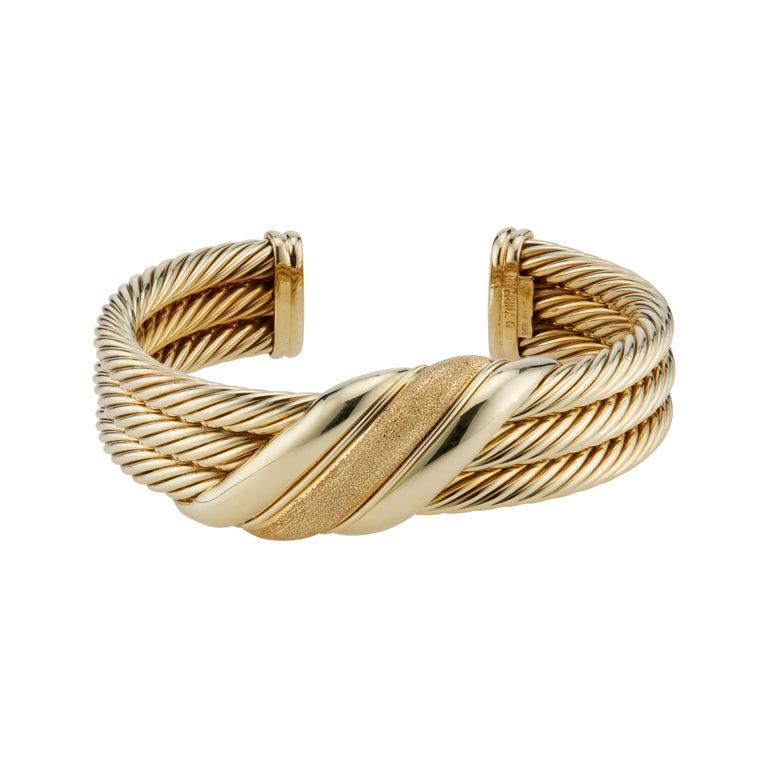 David Yurman Solid 14k yellow gold triple cable band cuff bracelet. Fits a 6.50-7 inch wrist.   14k yellow gold  Stamped: 14k Hallmark: D Yurman 51.8 grams  Width: 19/15mm Thickness/depth: 9.2/5.5mm Inside dimension: 2 3/8 inch x 2 Inch Shape: Oval