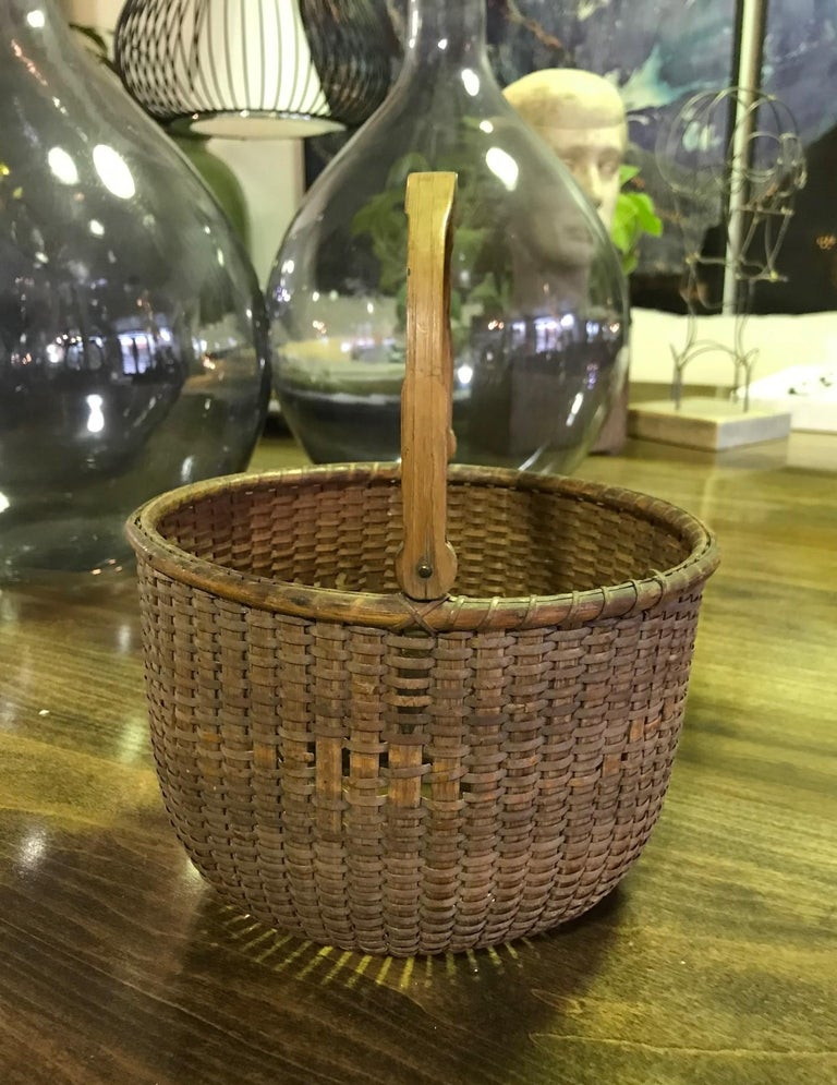 A wonderful and quite rare and hard to find Nantucket Lightship basket by Davis Hall, (1828-1906). Hall's baskets are prized by collectors of lightship baskets worldwide. This basket is made with his traditional swing handle and rounded lollipop