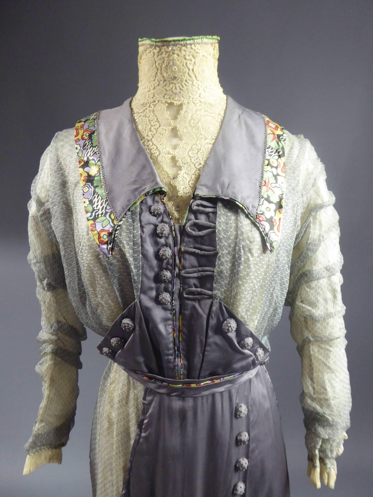 Circa 1905/1910  England   Beautiful day dress of the English bourgeoisie dating from the early twentieth century. Grey satin and muslin printed circular patterns. Effect of an apron and bib embellished with button in the same embroidered knot.