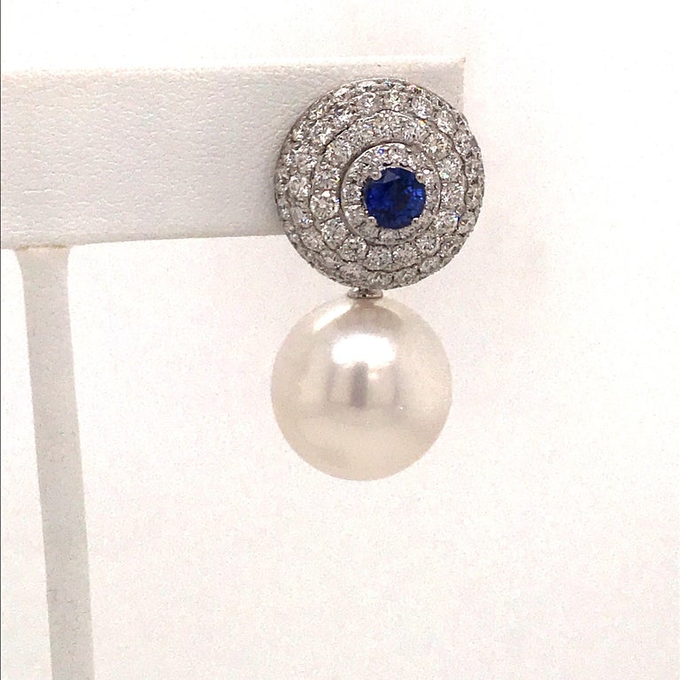 18K White gold earrings featuring 142 round brilliants weighing 3.75 carats with two center sapphires weighing 0.95 carats and white South Sea Pearls measuring 14-15 mm.