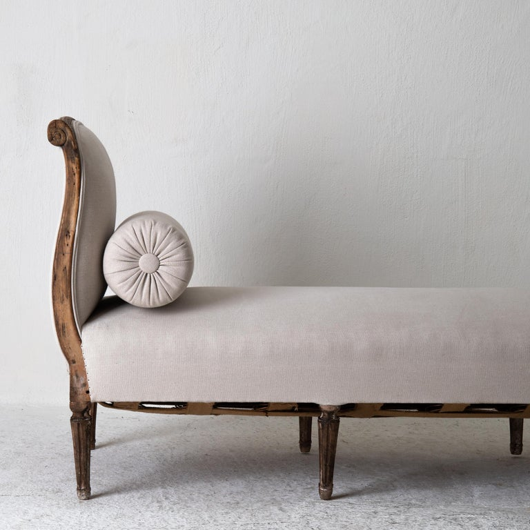 A daybed made during the early part of the Gustavian period in Sweden, 1780-1800. Frame made from dark stained wood carved with ribbon beading and flowers. Rounded and channeled legs. Upholstered in a neutral colored linen.