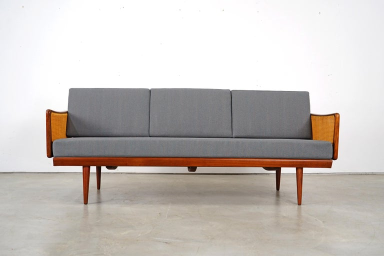 Rare classic of Scandinavian furniture by Peter Hvidt & Orla Mølgaard Nielsen. Teak and wicker frame. New foam upholstery covered with a beautiful fabric by ROHI. The daybed was produced by France & Søn in the 1960s. It is in every good condition.