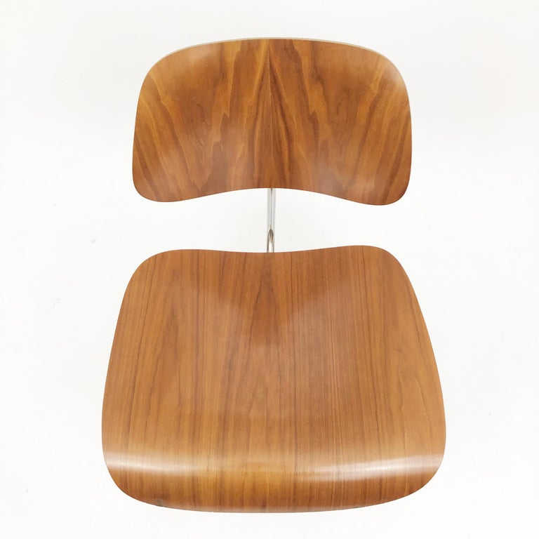 A set of 4 of beautifully grained early DCM chairs by Charles and Ray Eames for Herman Miller.  The latest patent number on the labels is from 1952. The foil label is also an early Herman Miller design.  Pressure-molded oak plywood on chromed