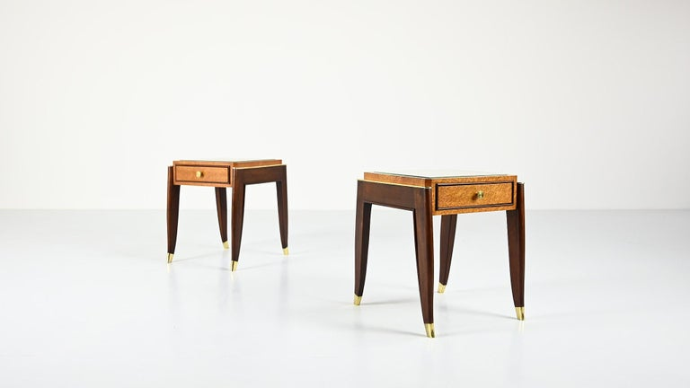 A beautiful pair of Art Déco nightstands or end tables, attributed to De Coene Frères. A top made of blonde Amboyna burl veneer and glass, displaying one drawer with a brass handle, supported by solid mahogany sabre legs with brass shoes. Veneer