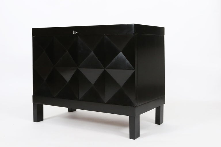 This small sideboard with geometric doors is executed by De Coene., Belgium in the 1970s. The credenza shows a pyramid like pattern on its doors. The squares on the front are each divided in four quarters and the chest features square. The interior