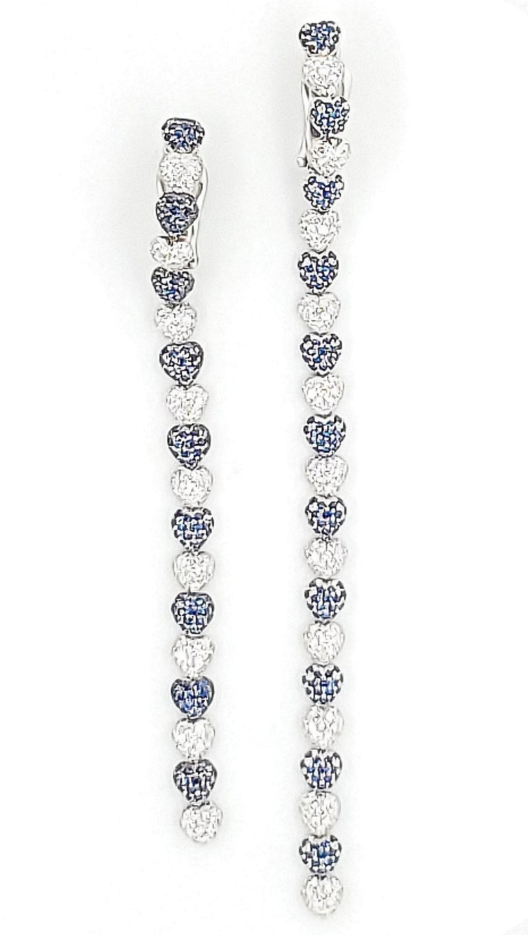 A pair of long heart motif earrings set with approx. 2.92 carats of round brilliant cut diamonds (F color, VS clarity) and 3.95 carats of sapphires. Earrings are asymmetrical lengths of 12.5mm and 10mm. Signed deGrisogono Geneva, 750. Collapsible