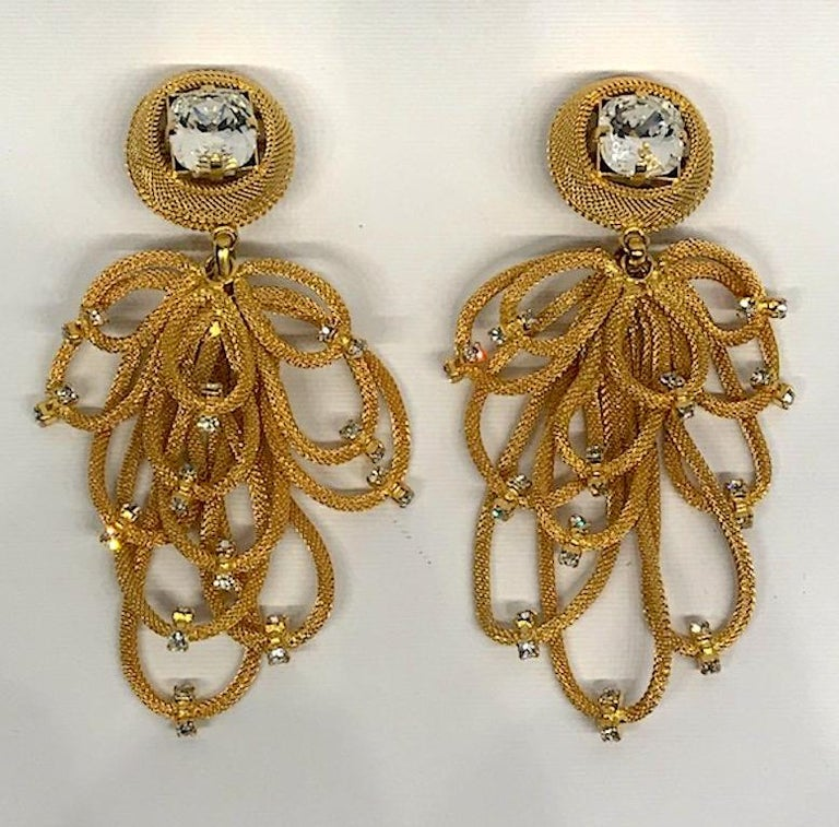 A dramatic pair of 1980s gold tone chandelier earrings of mesh loops with rhinestone accents by Italian fashion company Di Liguoro. Each pendant consist of 12 mesh tube cord loops in various lengths suspended from a mesh button top with large