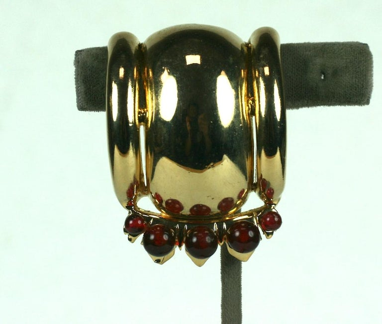 Ralph De Rosa Machine age 14 karat gold plated fur clip from the 1940's.  The Retro atomic half spherical clip is enhanced with two sizes of faux dark ruby beads.  Excellent Condition, Signed DeRosa. 1940's USA. L 2 1/16