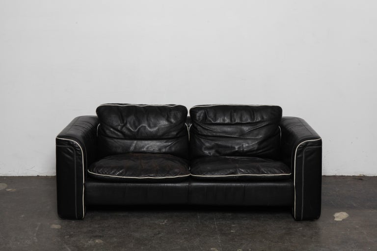 Black leather 2-seat sofa by De Sede with off white piping, in original leather. Swizterland, 1980s. Wear commensurate with age and use but in good vintage condition, no tears.