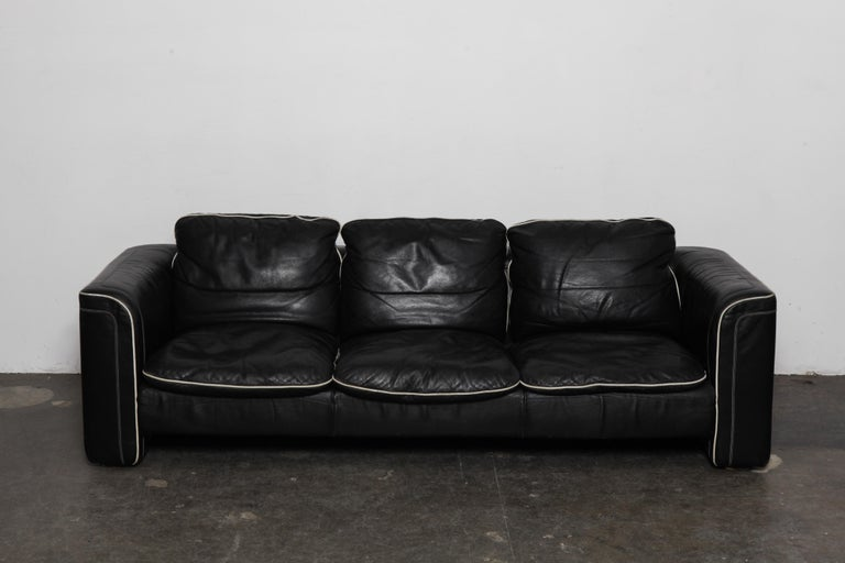 Black leather 3-seat sofa by De Sede with off white piping, in original leather. Swizterland, 1980s. Wear commensurate with age and use but in good vintage condition, no tears.