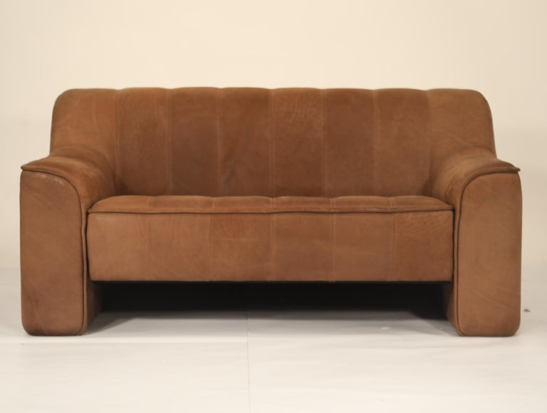 This incredible channel-tufted adjustable DS-44 settee sofa by De Sede, the leading Swiss design company since the 1960s, is skillfully crafted in Switzerland from thick, heavy, quality Buffalo leather.   The beautiful patina and vertical