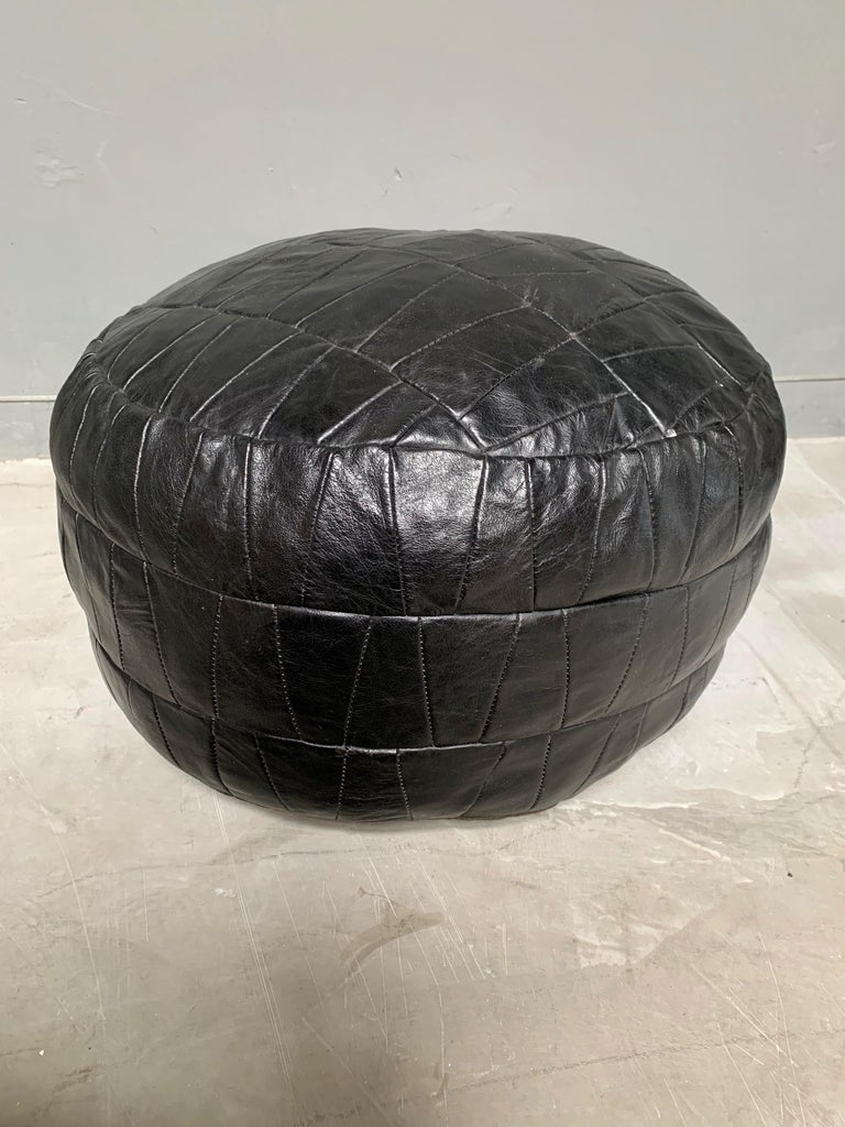 Great patchwork leather pouf by De Sede with black leather strips. Great coloring and patina to leather. Very good condition. Great accent piece.