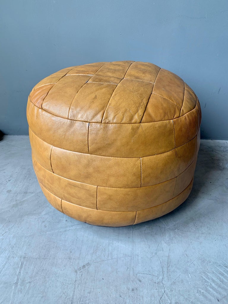 Unique patchwork leather ottoman by De Sede with camel colored leather strips. Great coloring and patina to leather. Very good condition. Great accent piece.