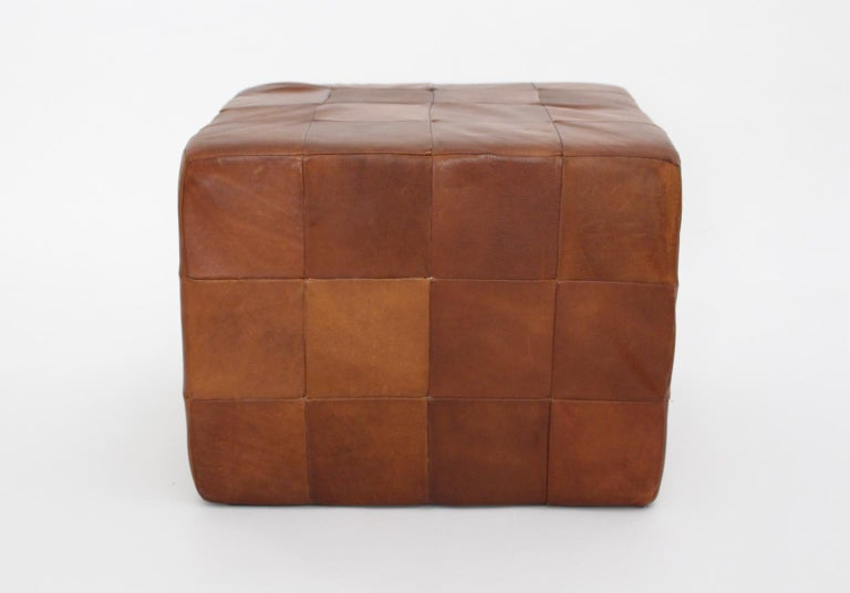 Cubus leather stool by De Sede Switzerland with beautiful leather patina. Many stitched leather pieces shape this cubus stool.  approx. measures: Width 53 cm Depth 53 cm Height 40 cm.