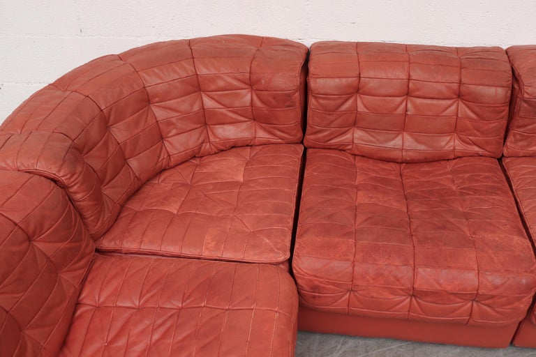 De Sede DS11 terracotta colored leather sectional sofa. Impressive 7-piece patchwork leather sectional. In original condition with visible signs of wear with visible scratching, some staining and wear. Wear is consistent with its age and use. Color