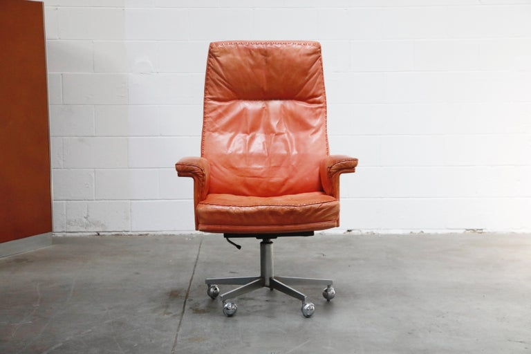 Beautiful distressed leather on this vintage De Sede DS35 highback executive desk chair on casters. This incredible office chair features an extremely comfortable form, burnt orange color aniline leather upholstery with whipstitch edge detail,