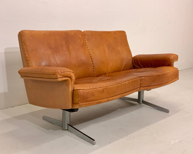 This very rare iconic Mid-Century Modern leather lounge sofa is from the renowned leather manufacturer De Sede (Switzerland) and a popular 1960s-1970s vintage design Classic. It comes in smooth and soft aniline cognac brown leather and is from