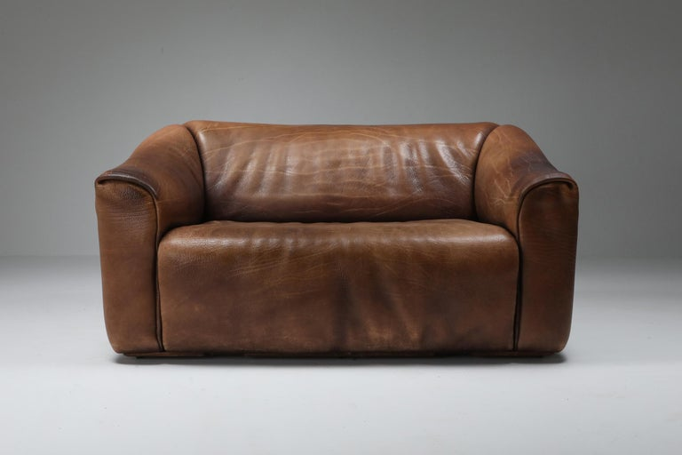 Brown leather two-seat sofa by Swiss manufacturer De Sede. Bullhide leather with retractable seating for an even more comfortable seat. The DS 47 model is a true design Classic and is still in production. This is an original model with tons of