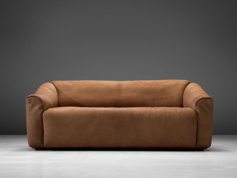 Highly comfortable DS47 sofa in light cognac leather by De Sede. The design is simplistic, yet very modern. A tight and cubic outside with a soft and curved inside, which emphasize the comfortable character of this set. The thick leather is laid in