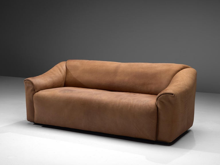 De Sede, DS-47 two-seat sofa, leather, Switzerland, 1960s.  Highly comfortable DS47 sofa in light cognac leather by De Sede. The design is simplistic, yet very modern. A tight and cubic outside with a soft and curved inside, which emphasize the