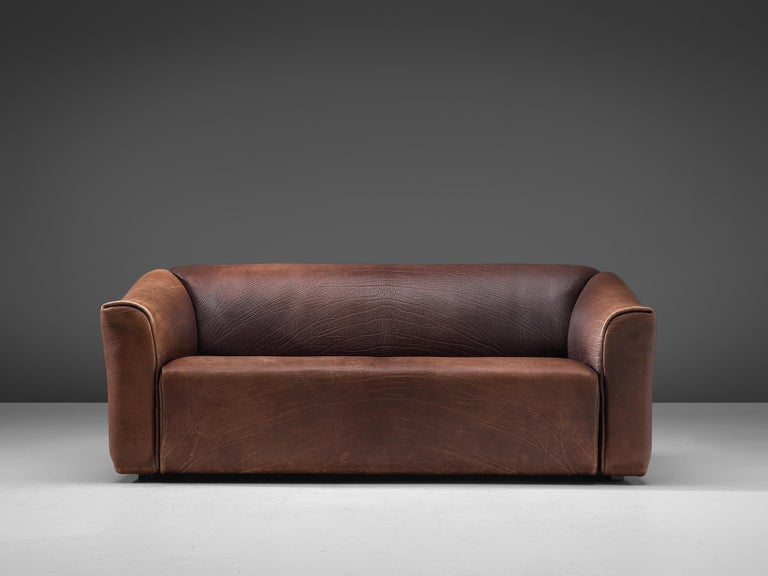 De Sede, DS-47 two-seat sofa, buffalo leather, Switzerland, 1970s.  Highly comfortable DS47 sofa in chocolate brown leather by De Sede. The design is simplistic, yet very modern. A tight and cubic outside with a soft and curved inside, which