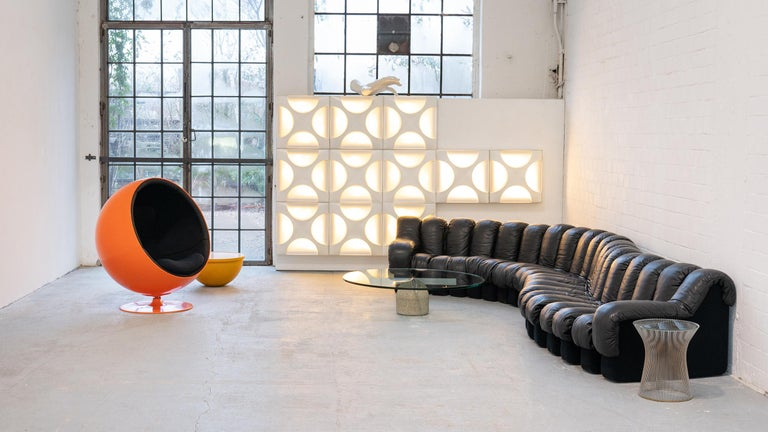 Designed by Ueli Berger, Eleonore Peduzzi Riva, Heinz Ulrich + Klaus Vogt in 1972.  It consists of 20 black elements, 2 of them are armrest elements. All elements have black felt bases with a numbered base.  A sofa with multiple configuration