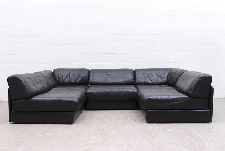 Handsome De Sede DS 76 black leather 5 piece sectional sleeper sofa with deep zip-on cushions that fold out to beds. A few well loved sections with visible wear and some cracking to seat. A few minor tears. Measurements shown are as seen in 1st