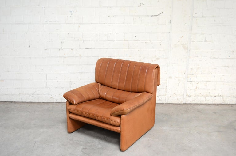 Vintage leather Armchair by De Sede. Model Ds 86. Thick neck leather with beautiful cognac color. Great comfort. With patina. On the left side the leather color is faded also the back. De Sede is a Switzerland furniture company that creates