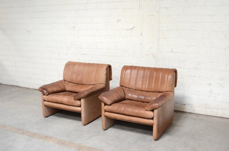 Vintage leather armchair by De Sede. Set of 2 Model Ds 86. Thick neck leather with bright nature brown color. Great comfort. With patina on the armrests. De Sede is a Switzerland furniture company that creates leather furniture with premium