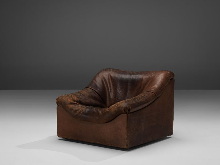 De Sede, DS46 lounge chair, brown leather, Switzerland, 1970s  Comfortable lounge chair in thick buffalo leather by De Sede. This model features a solid base with a rounded, bulky seat and a high back. The piece is in original condition and the