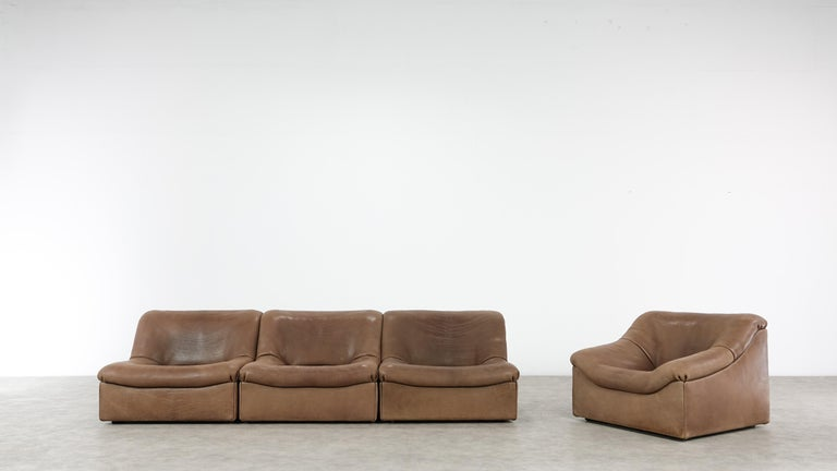 Cognac colored original De Sede DS designer leather corner sofa and one easychair in a minimalistic and modern design, with a convenient modular function, made for pure comfort and flexibility.
