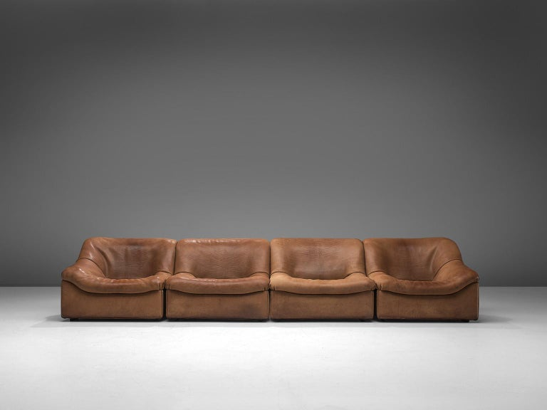 De Sede, DS46 sectional sofa with ottoman, cognac buffalo leather, Switzerland, 1970s.  Comfortable four-modular sectional sofa with ottoman in thick buffalo leather by De Sede. This model features a solid base with a rounded, bulky seat and a