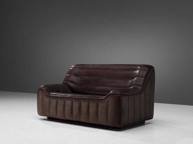 De Sede, 'DS84' sofa, leather, Switzerland, 1970s  Highly comfortable DS84 settee in dark brown leather by De Sede. The design is simplistic, yet very modern. This model features a solid base with a bulky seat and a high back. The armrests flow over