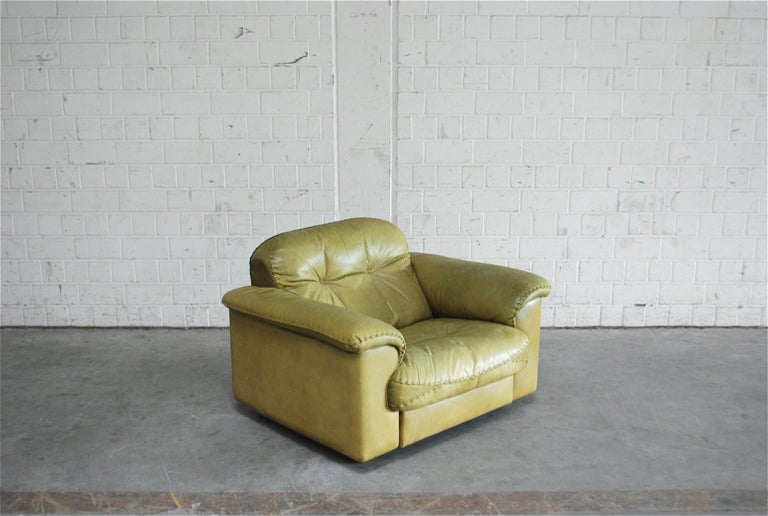 De Sede leather lounge armchair DS 101. Aniline leather in olive green. Great comfort with an extendable seat for much more lounge comfort. Known from the James Bond movie