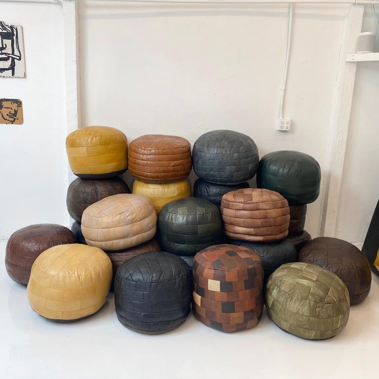 Massive collection of vintage leather poufs by De Sede of Switzerland. Perfect for a living room, boutique hotel or retail store. Good vintage condition. Wear and patina vary throughout.   24 unique poufs, priced individually in separate listings.