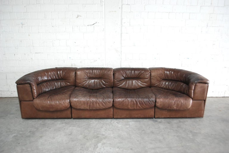 De Sede module sofa in brown leather. Vintage condition. It consists of 4 elements including 2 end and 2 single elements. It can be transformed in different variations like a 3-seat sofa and 1 chair or a 4-seat sofa. De Sede is known for best