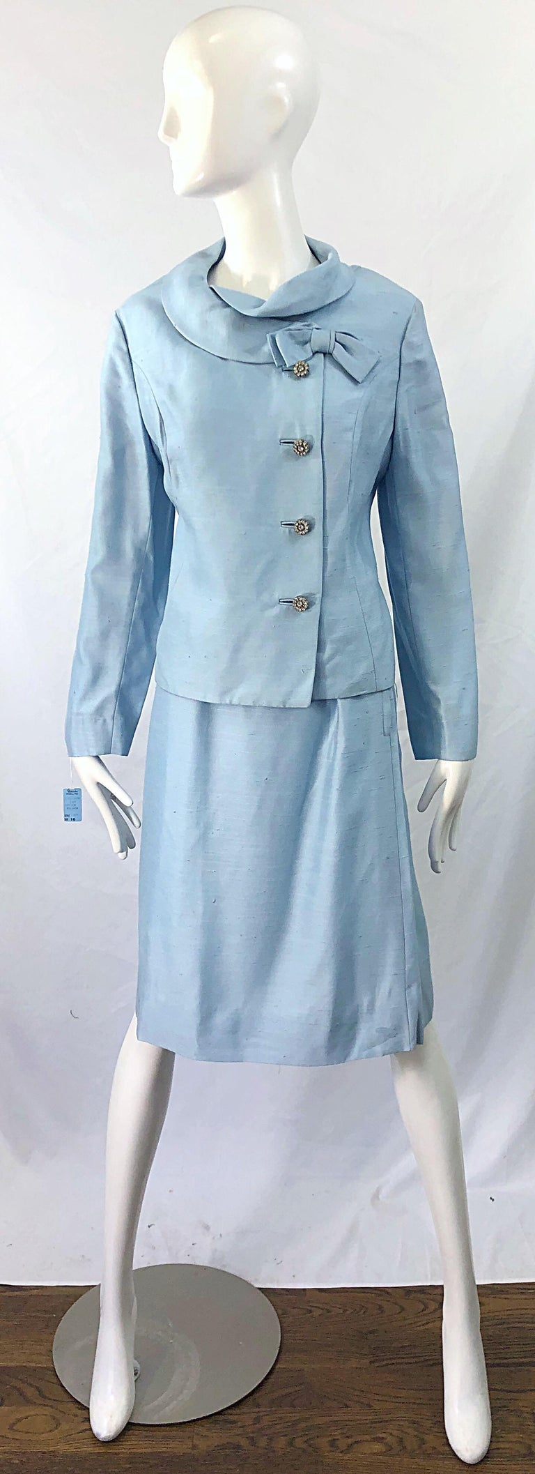 Chic deadstock ( brand new with tags ) original 1960s Alvin Handmacher ( Weathervane Tailored by Handmacher ) baby blue skirt suit ! Features a tailored jacket with pre--tied bow at left collar. Rhinestone encrusted buttons up the front. High