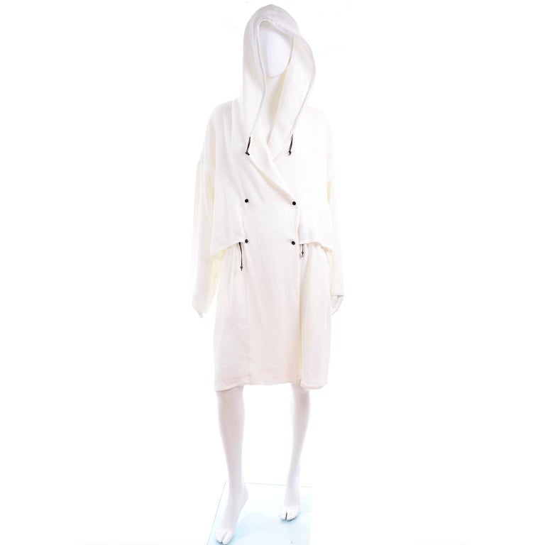 This is a gorgeous 100% linen drawstring hooded jacket from Dusan.  The coat is white with black drawstrings at the hood and waist. It crosses over to close with double breasted small black buttons. This luxe linen coat is deadstock with its