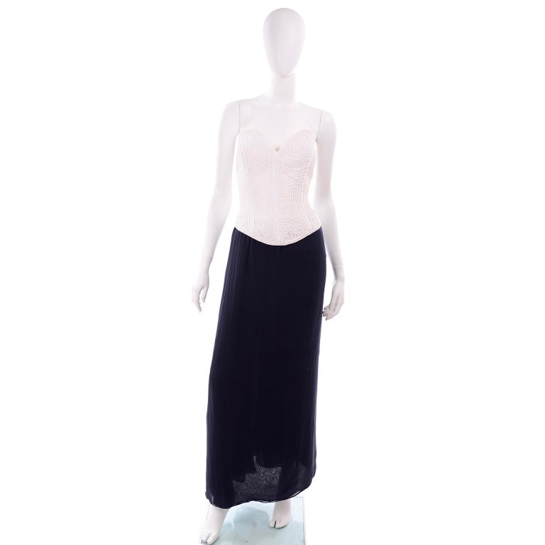 This is a vintage deadstock Oscar de la Renta evening ensemble that includes a ribbed white bustier style top and bolero jacket paired with a navy blue silk chiffon full length skirt. The white ribbed cotton bustier has an inner corset with cups,
