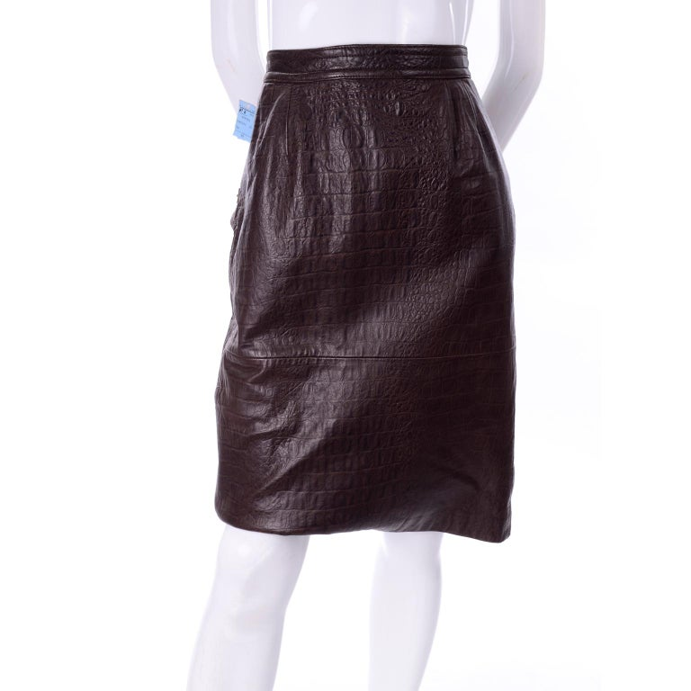 This is a gorgeous brown leather pencil skirt by Valentino with an alligator print embossing. It buttons and zips in the back, with two side flap pockets that button closed with two large buttons. It has a small kick flap in back and is fully lined