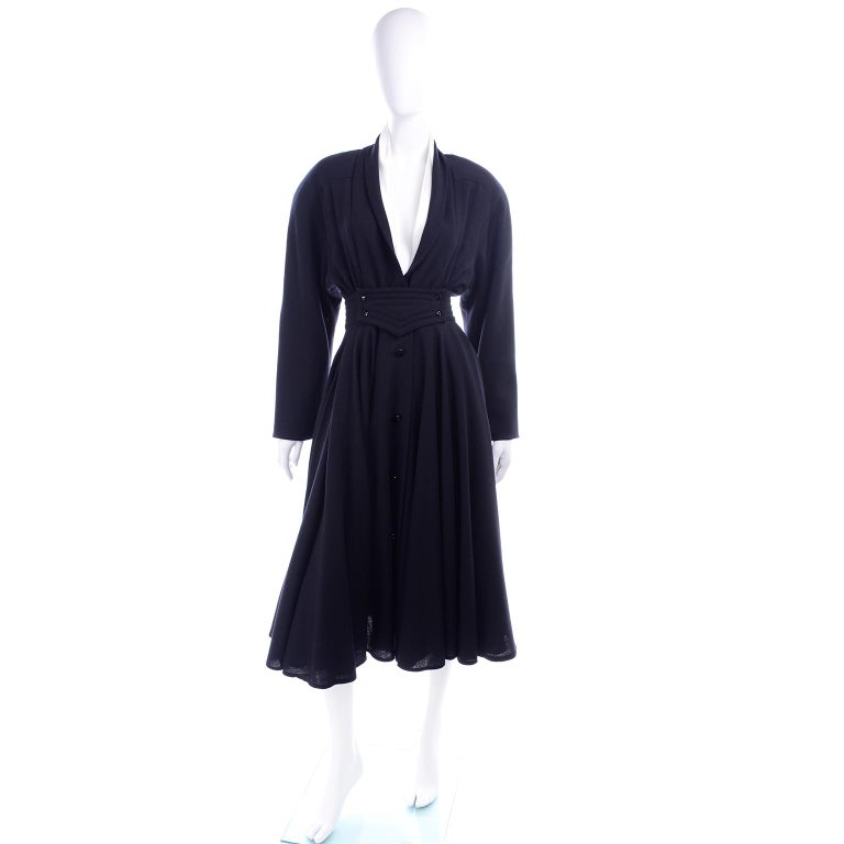 This dress is very hard to capture in photographs, but it is a stunning vintage wool Wayne Clark dress with a full skirt and a cinched waist.  The dress has buttons down the front and a detailed waist accentuated with a wide waistband and buttons.