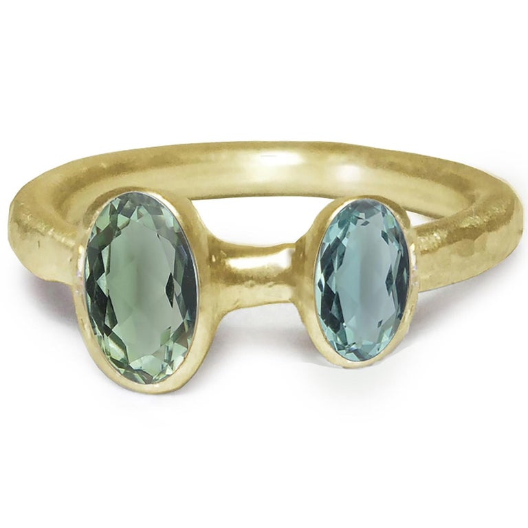 18 Karat Yellow Gold Ring by Deborah Murdoch is from the Abundance Collection featuring two oval Blue/Green Tourmaline Stones. The ring band is slightly planished giving that textural feel and has a silky satin finish.   Metal: 18 Karat Yellow Gold